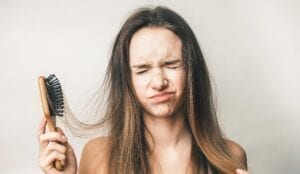 woman pulling her hair with hair comb